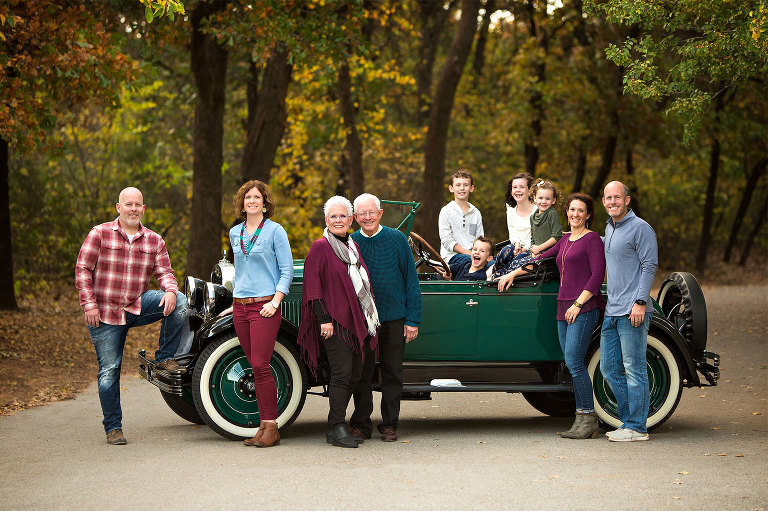 Extended family portraits with antique Chevrolet car